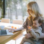 single mom carrying her baby and using laptop for online dating