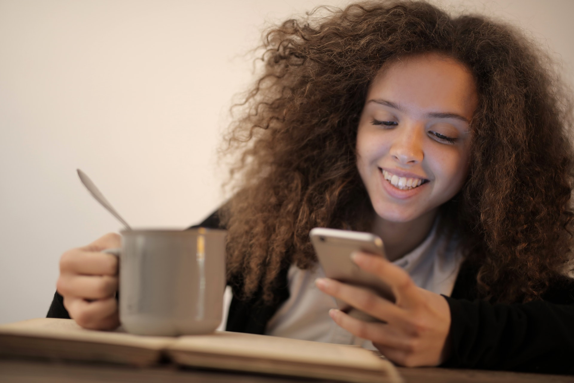 happy woman using mobile app with a cup on her hand