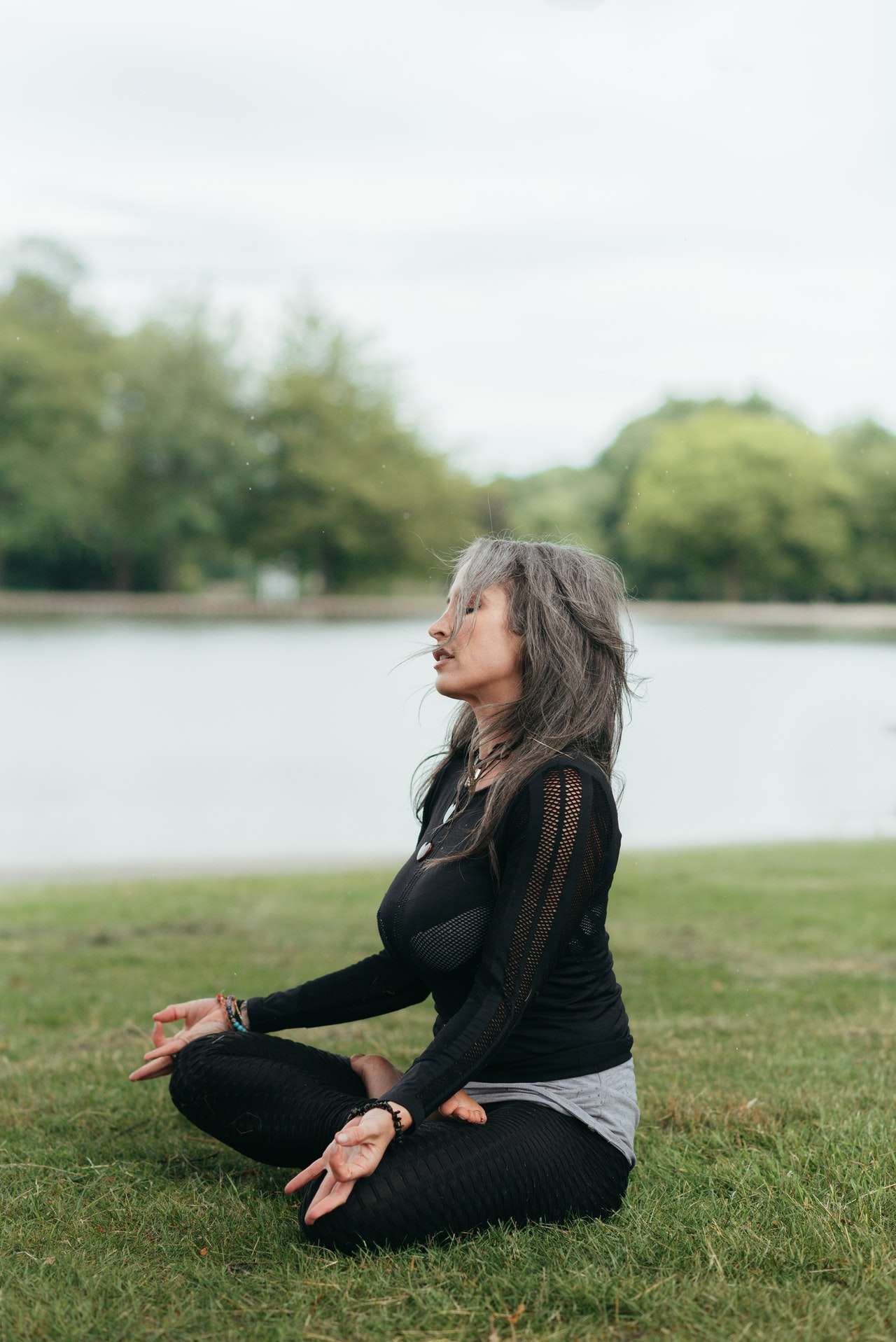 woman in grey hair wearing black and doing meditation