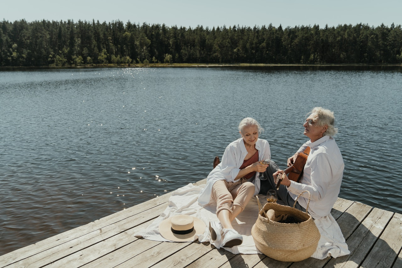 senior man and woman sitting on wooden dock