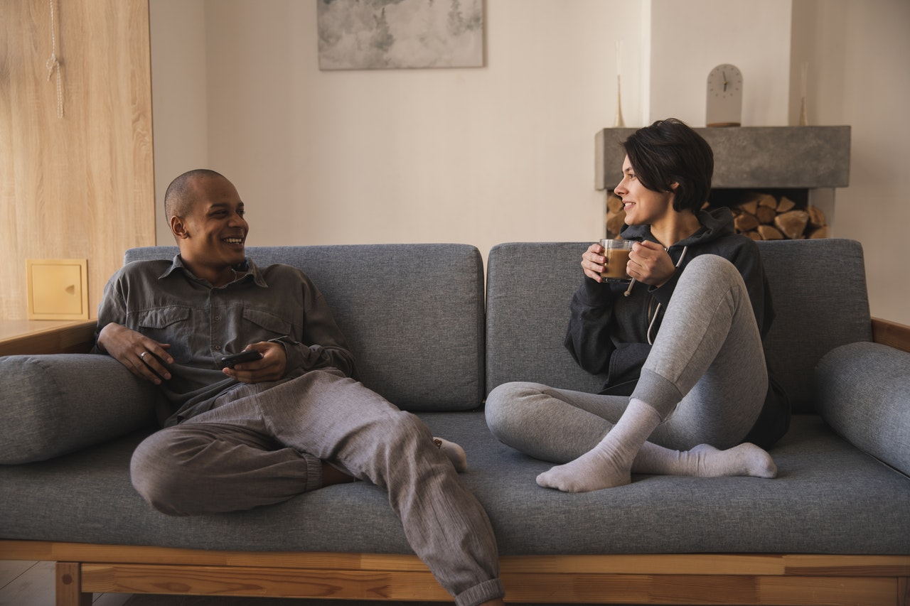 photo of an interracial couple sitting on sofa and laughing