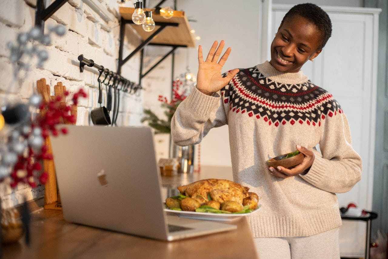 a black woman waving hand in front of a laptop