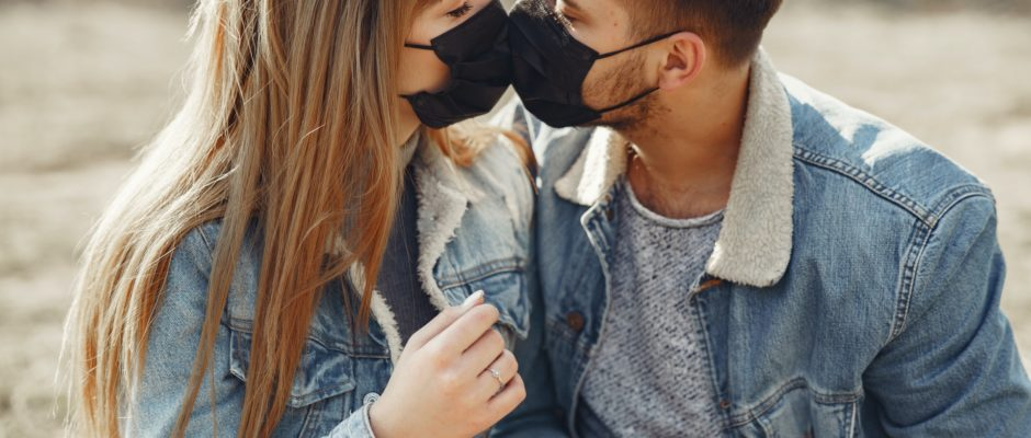 young couple wearing masks and kissing