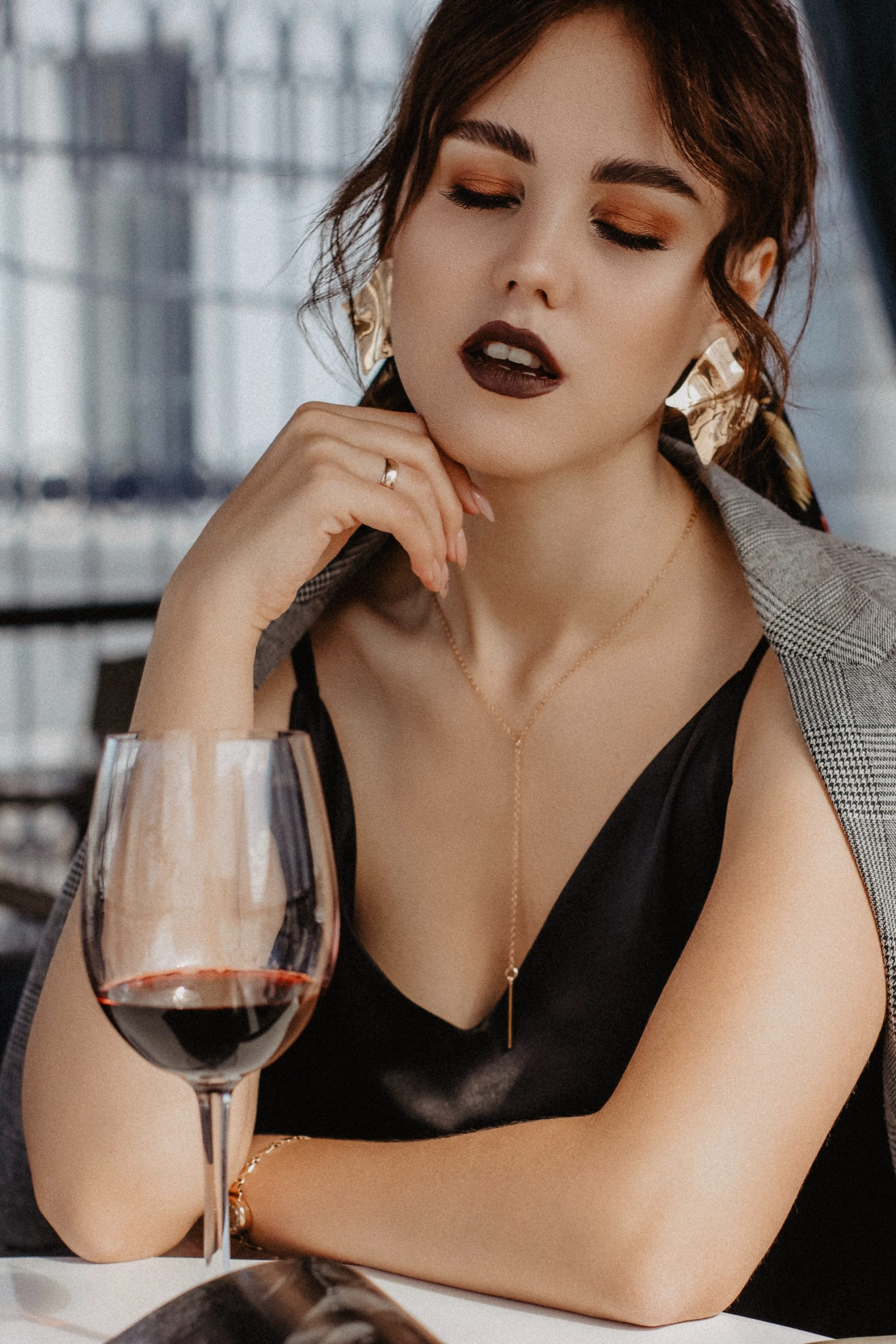 slurring young woman chilling in front of a glass of red wine