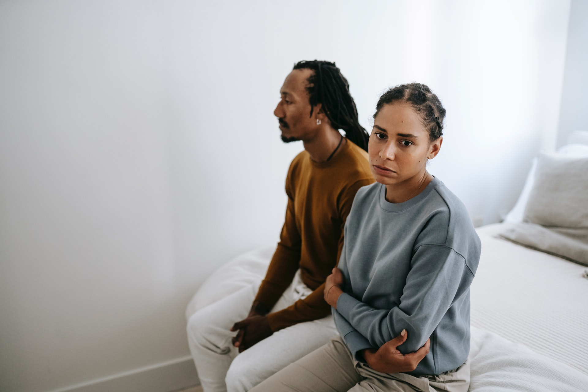 a man and a woman sitting on bed looking sad