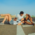 a woman laying on the road on a man's lap