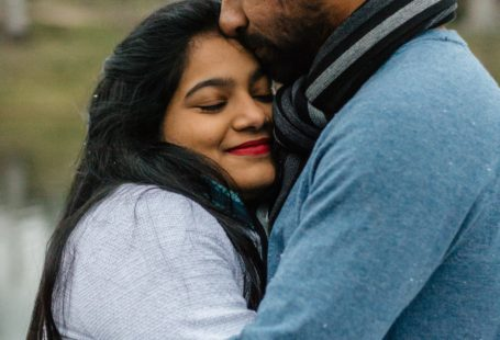 Man in blue hugging a smiling woman