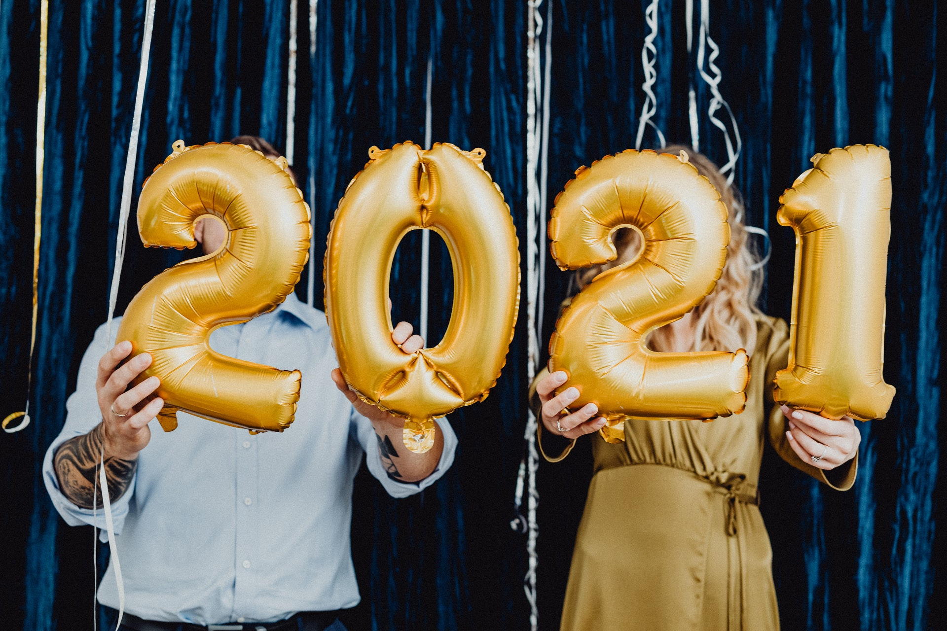 a man and a woman holding 2021 golden balloons