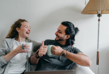 happy couple laughing on a couch and drinking coffee