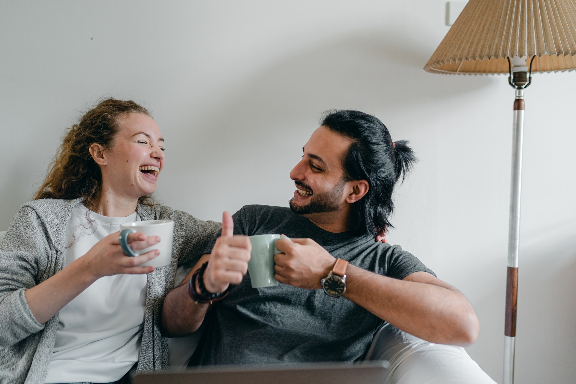 happy couple laughing on a couch and drinking coffee, having a deep conversation