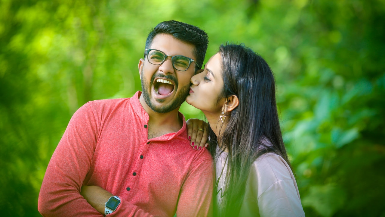 Indian woman kisses on Indian man's cheek