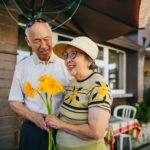 an elderly mature couple holding a bouquet of flower while holding hands