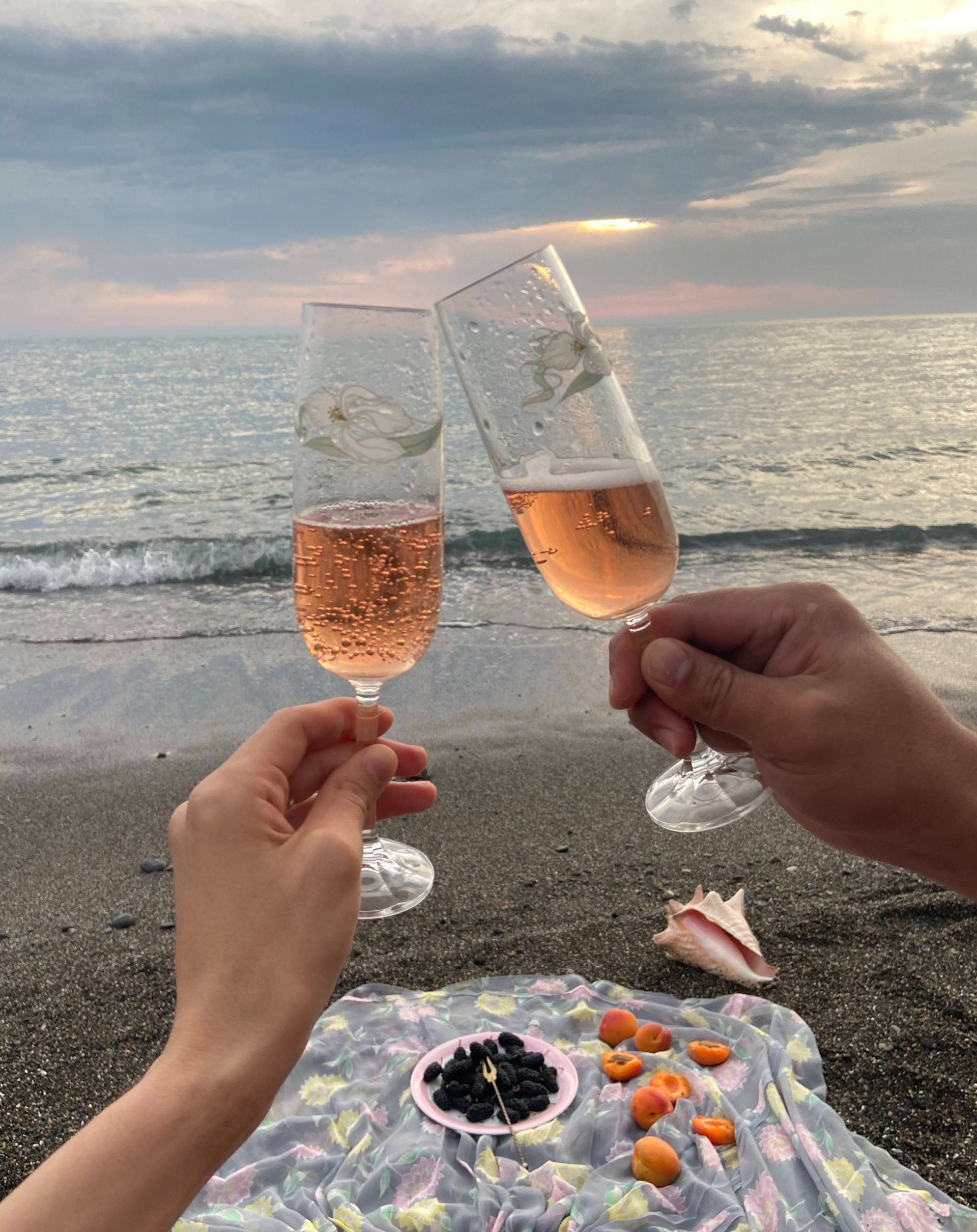 couple drinking glasses of champagne by seashore