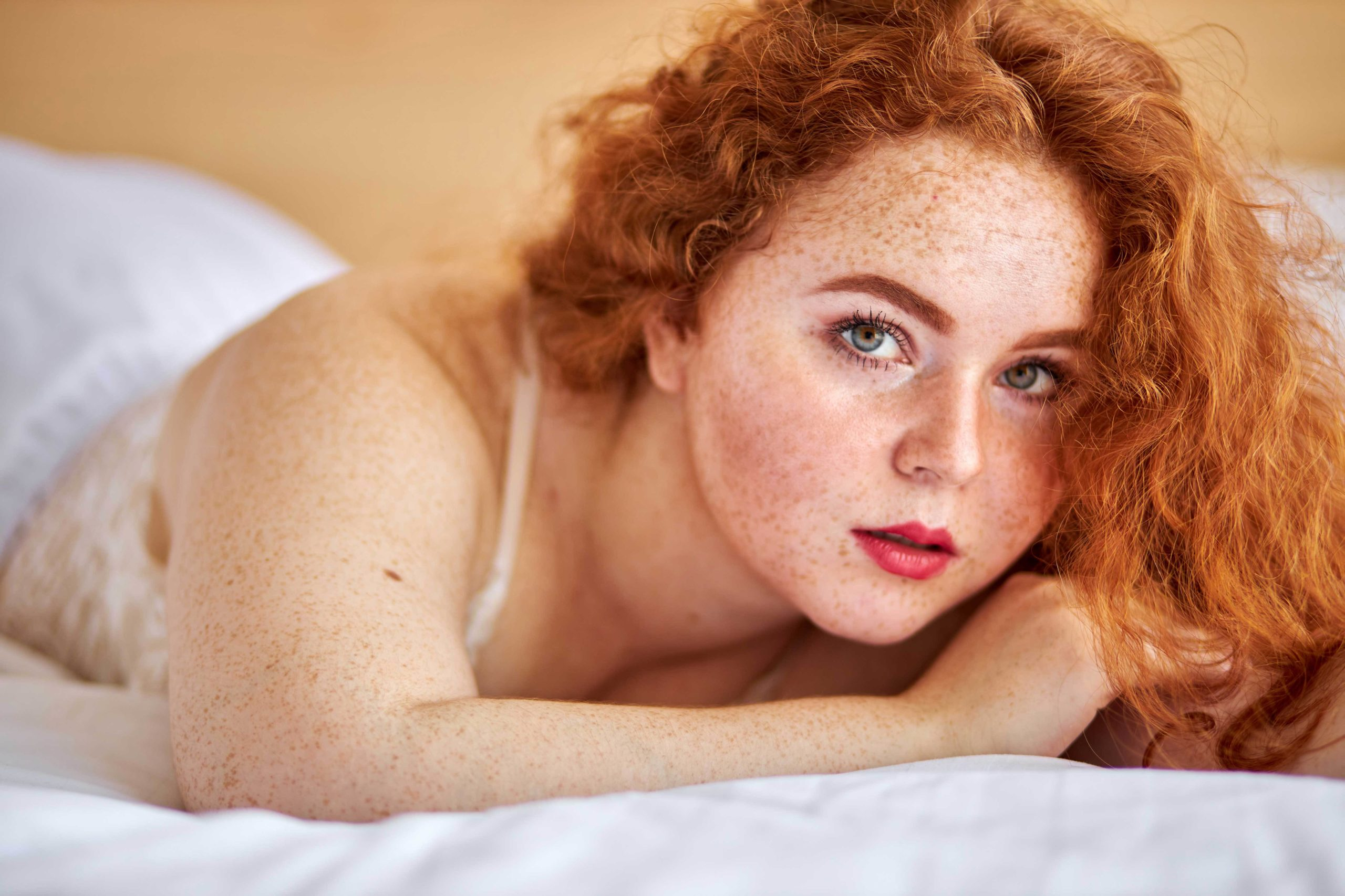BBW overweight pretty caucasian woman showing off fat figure wearing sexy lingerie, lying on bed relaxing, sexy redhead female at home