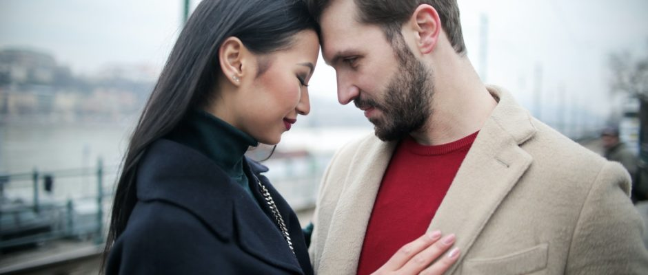 an asian woman in black holding a western man