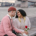 Hispanic couple with rose sitting on embankment