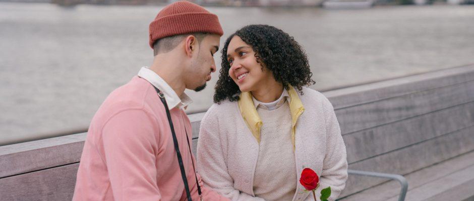 Hispanic couple with rose sitting on embankment