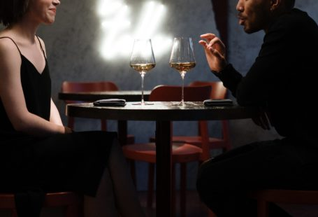 man and woman siting on chair in front of table