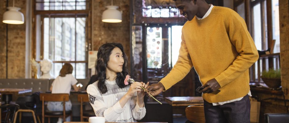a black man giving flower to an asian woman on their first date at a coffee