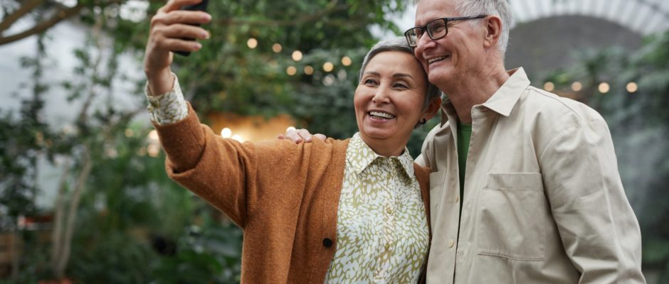 senior couple smiling while taking a sefie