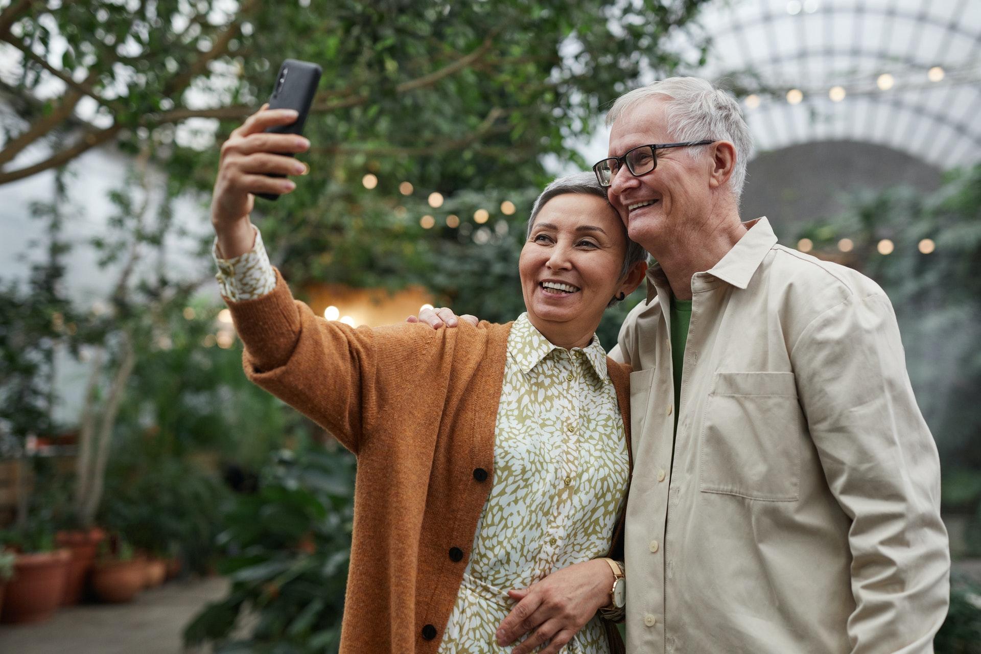 senior couple smiling while taking a sefie