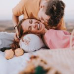 a woman smile happily while her boy friend kiss her cheek