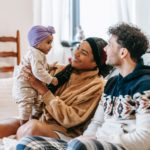 delight diverse parents sitting on sofa with cute baby