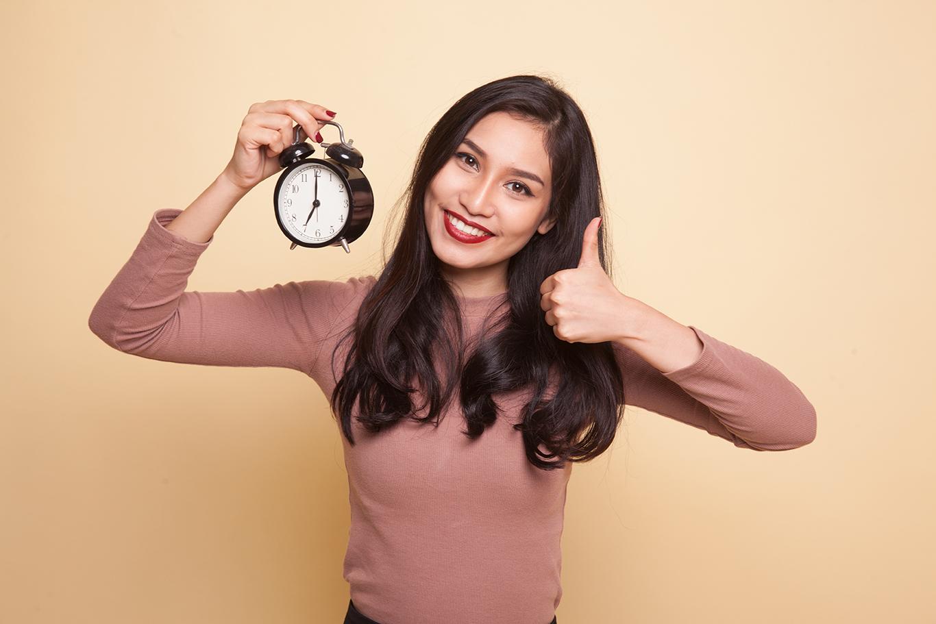 a latina holding a clock and thumb up