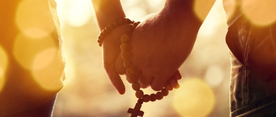 Christian Dating Couple praying together. Holding rosary in hand.