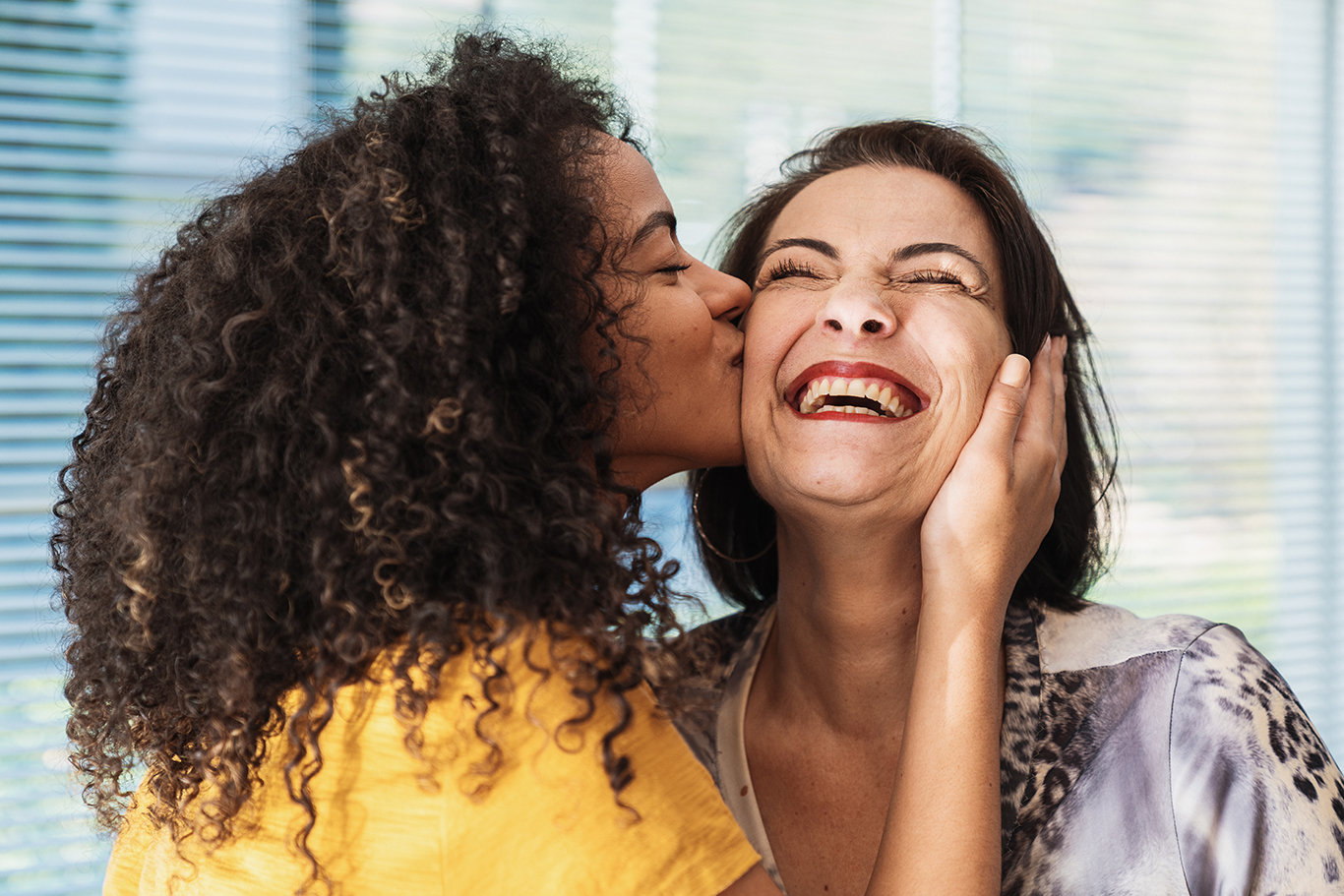 happy latin american family. curly-haired daughter kissing her mother