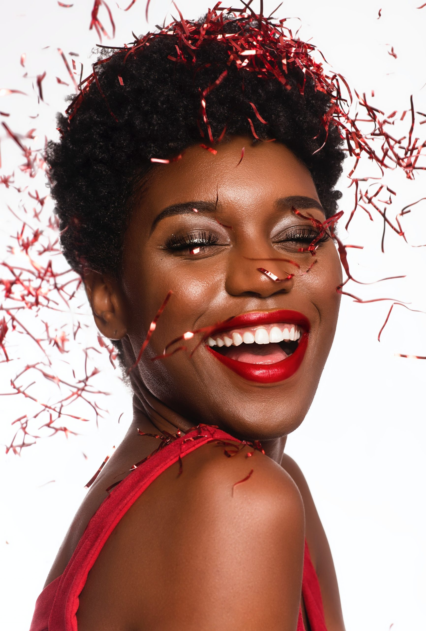 a close-up photo of a happy woman posting as confetti drop down her face