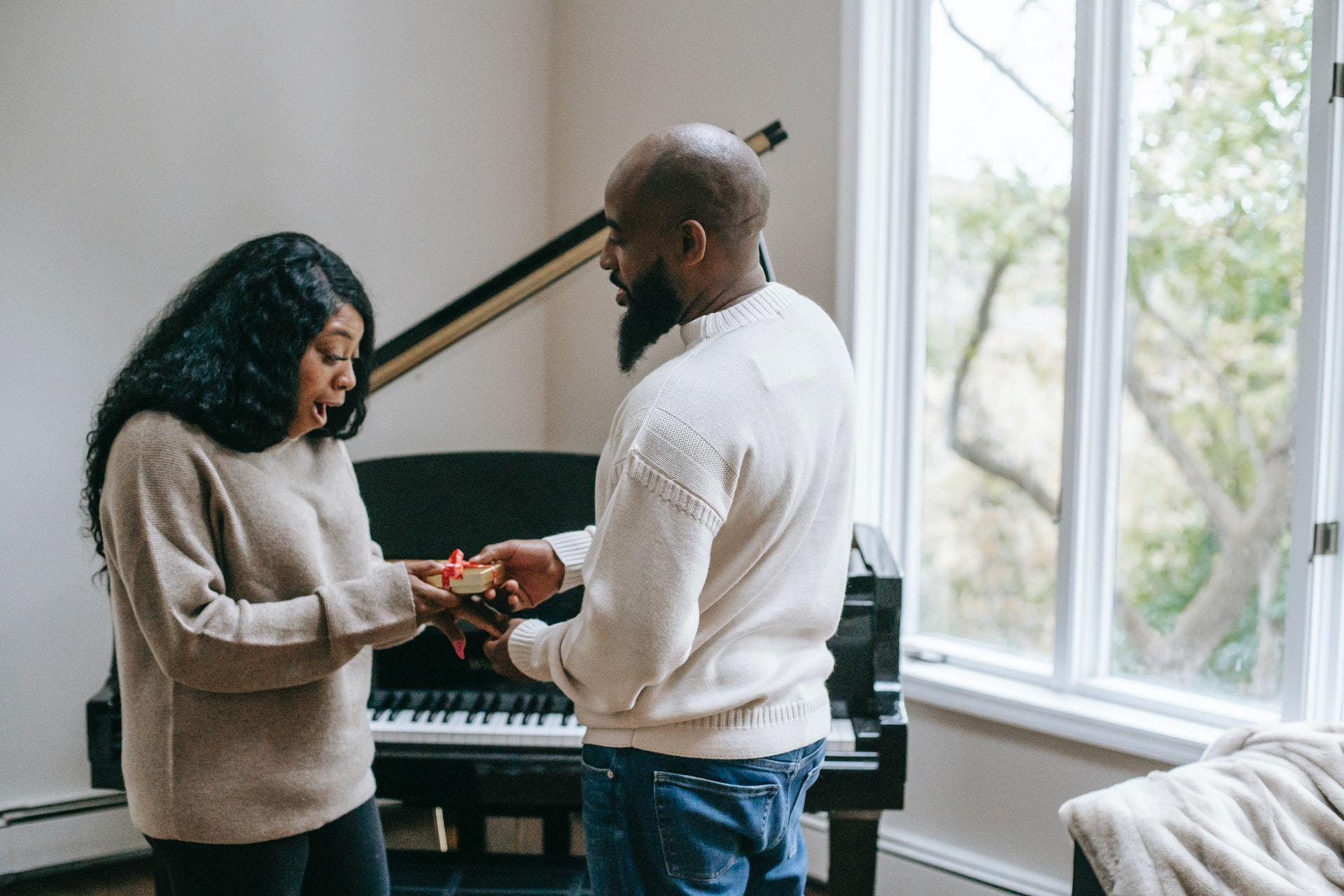 a black man giving gift to a black woman