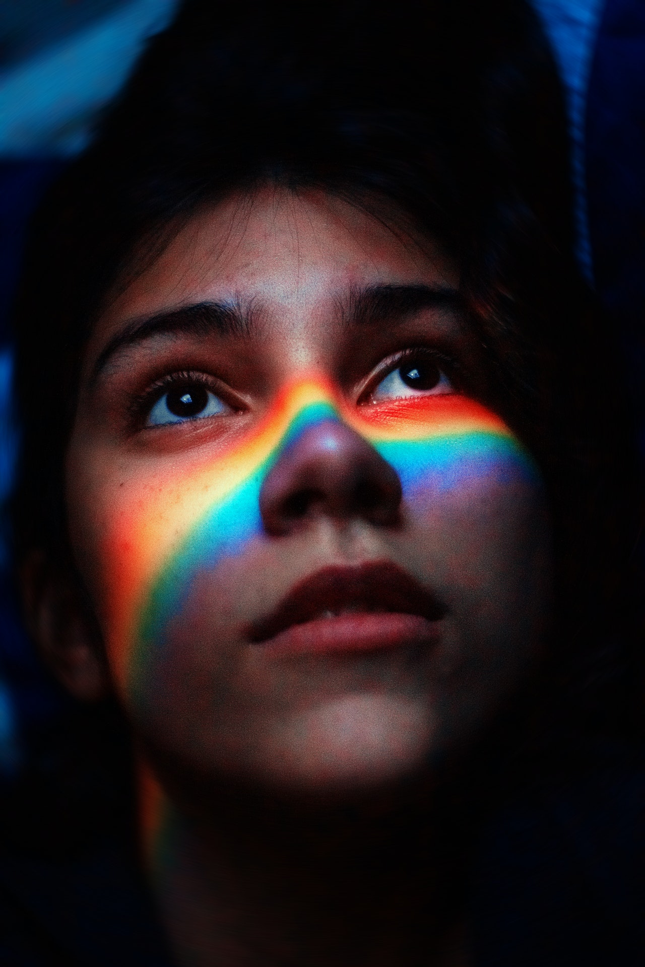 a close up photo of a lesbian girl face in shadow of LGBT rainbow color