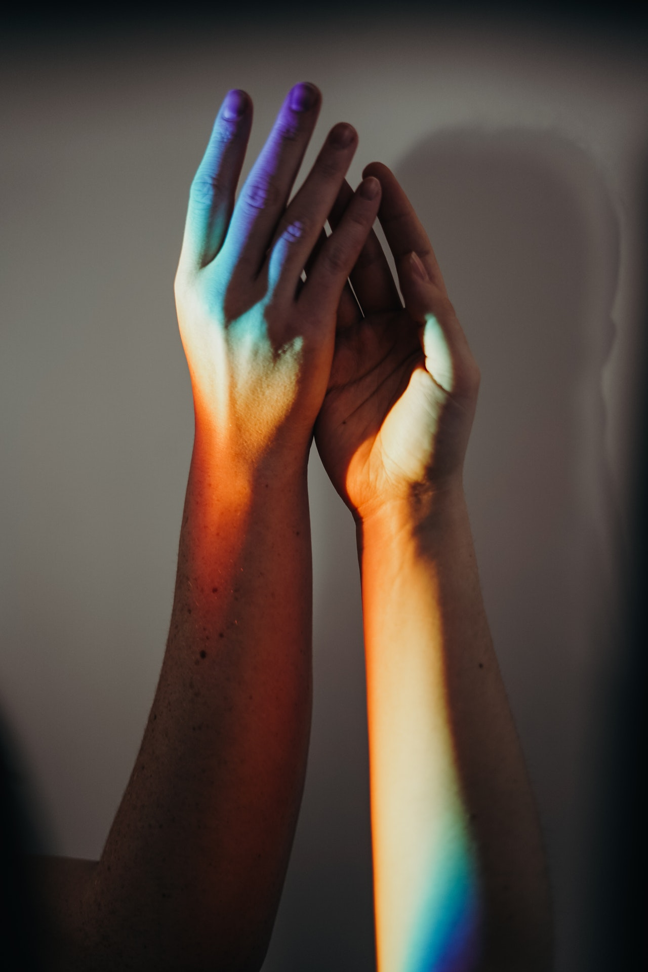 a close up photo of 2 hands holding in a shadow of LGBT rainbow color