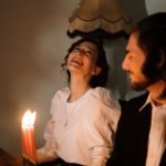 a happy woman in white shirt dating a Jewish man by candles