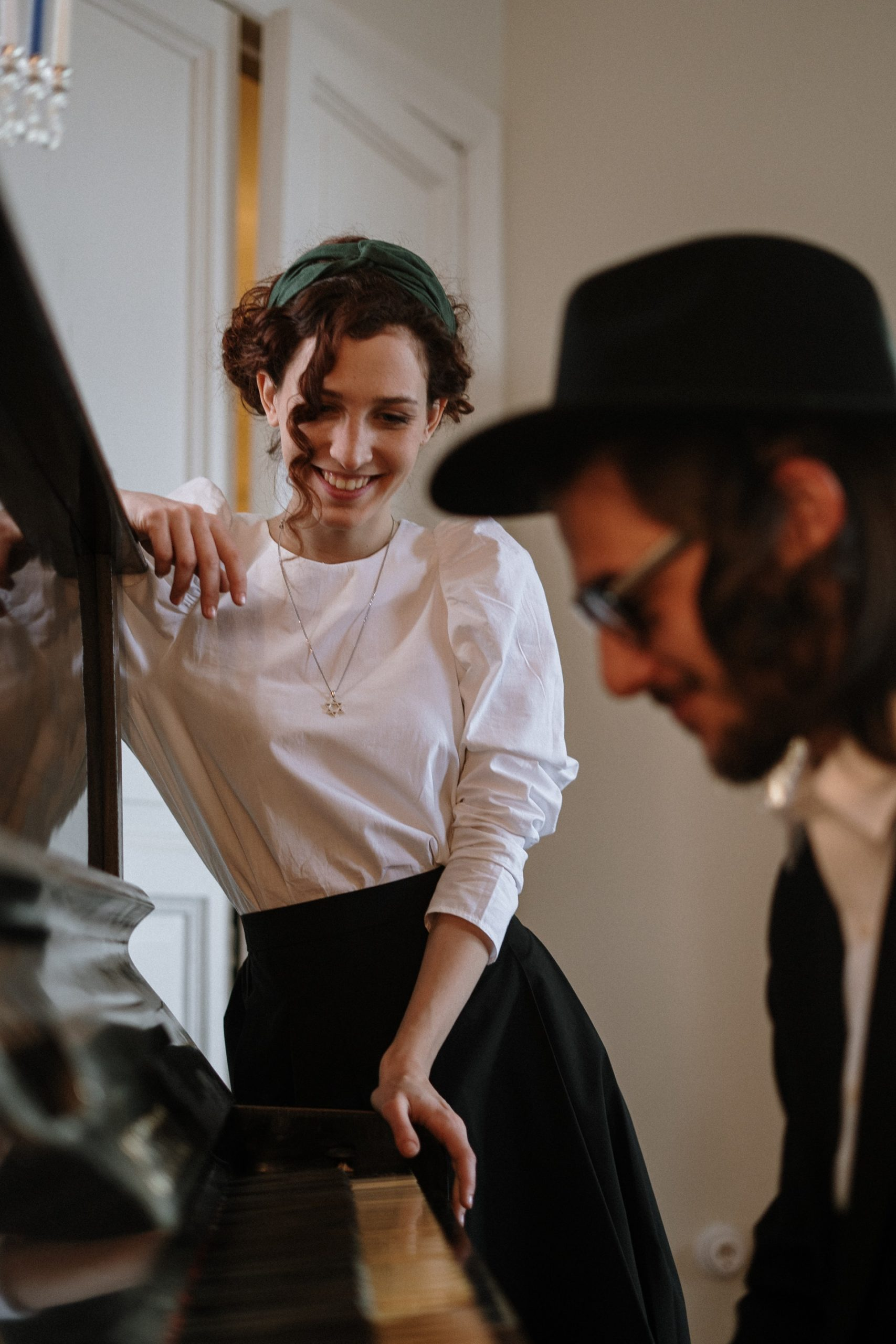 a woman in white shirt dating a Jewish man who is playing a piano