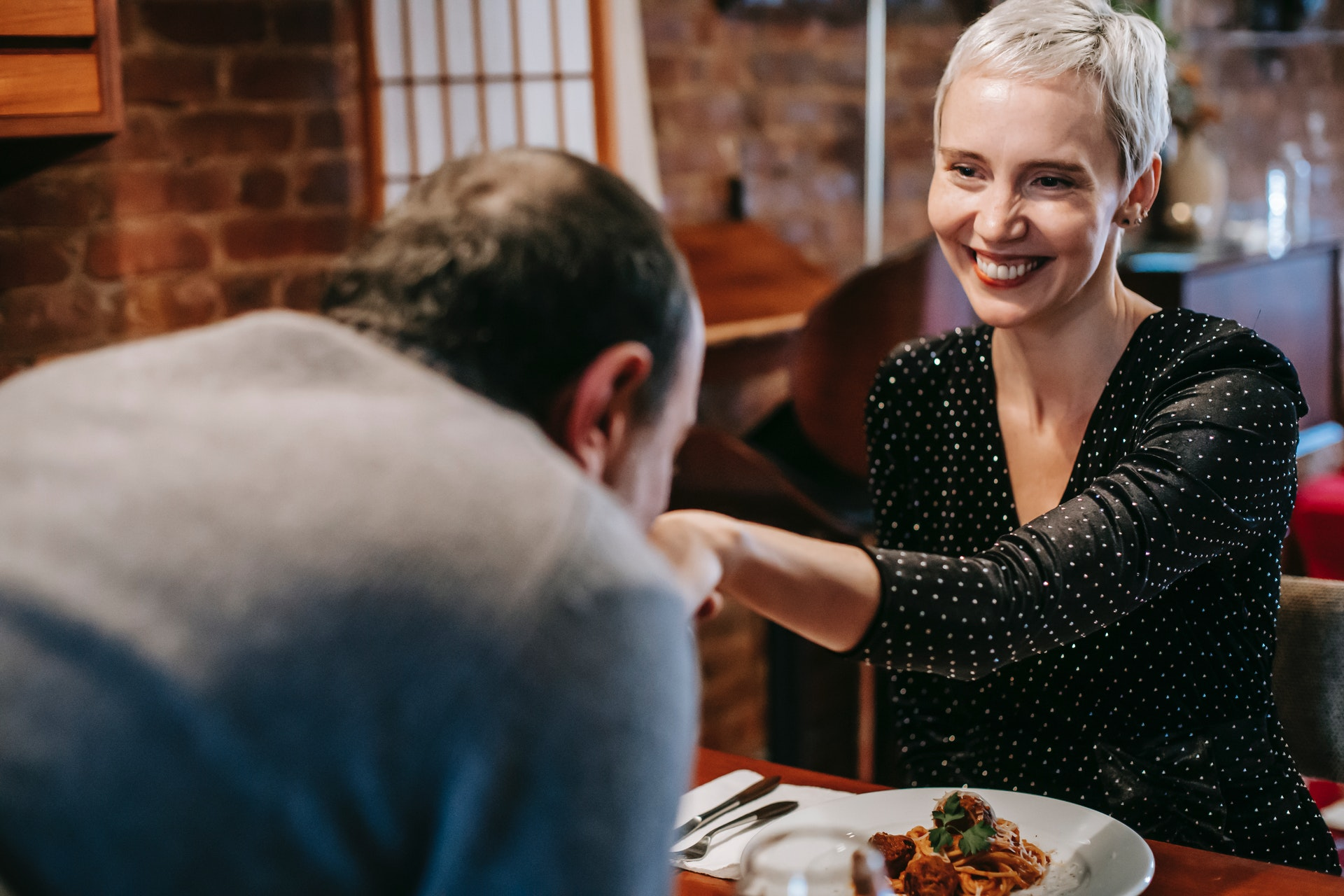 a couple having dinner in a restaurant and the man kissing the woman's hand