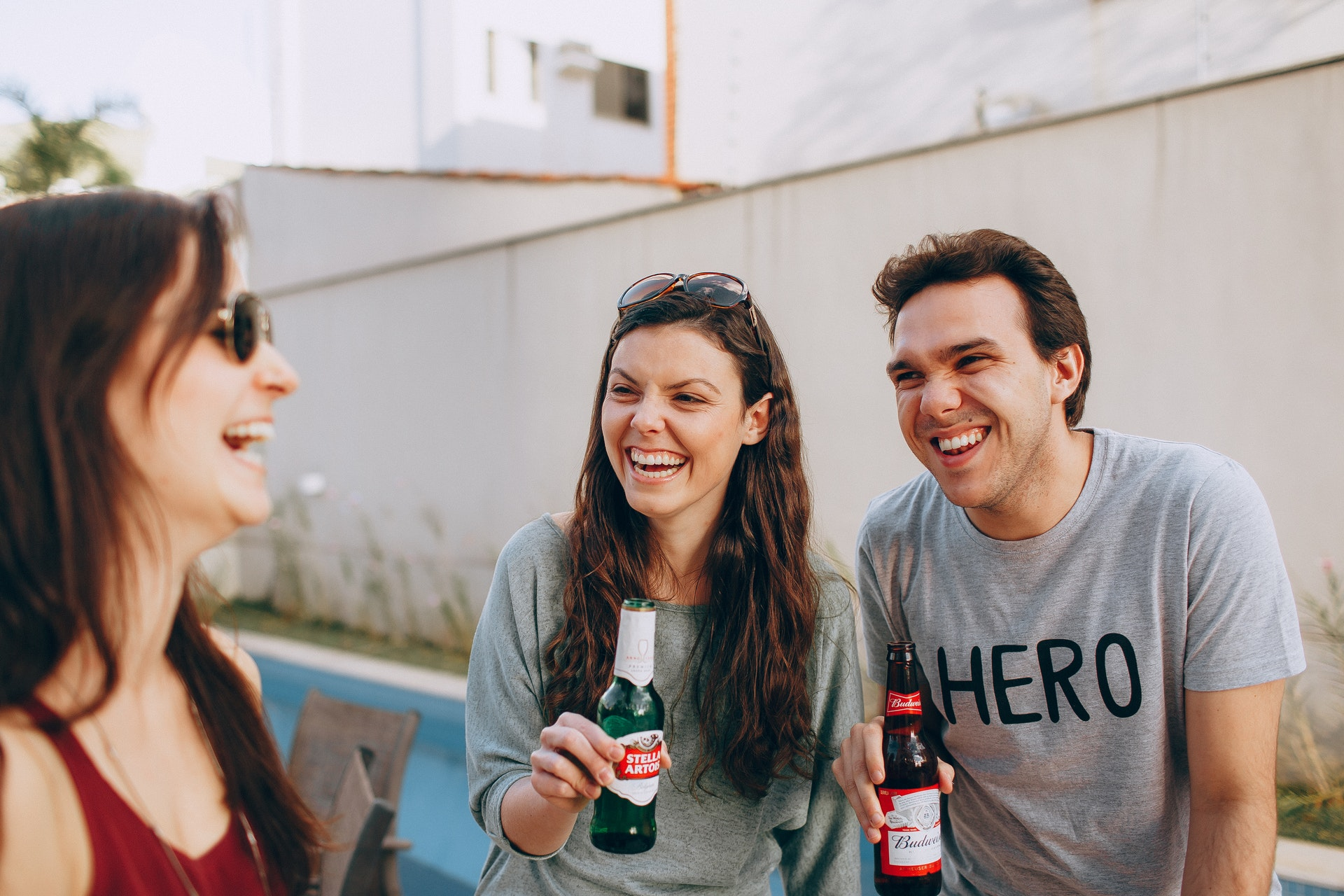 a couple and their friend holding beers and laughing