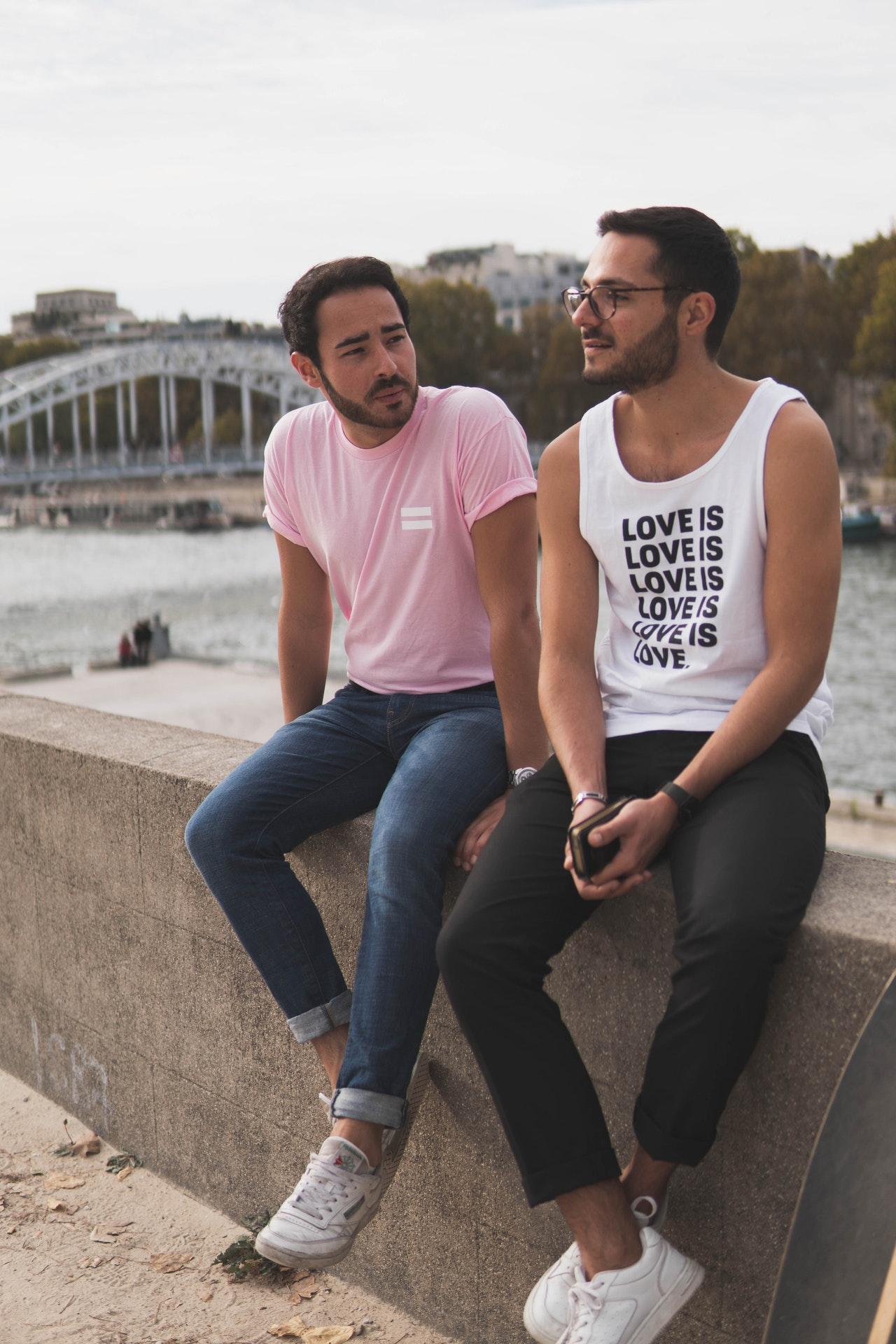 2 gay men sit down next to each other