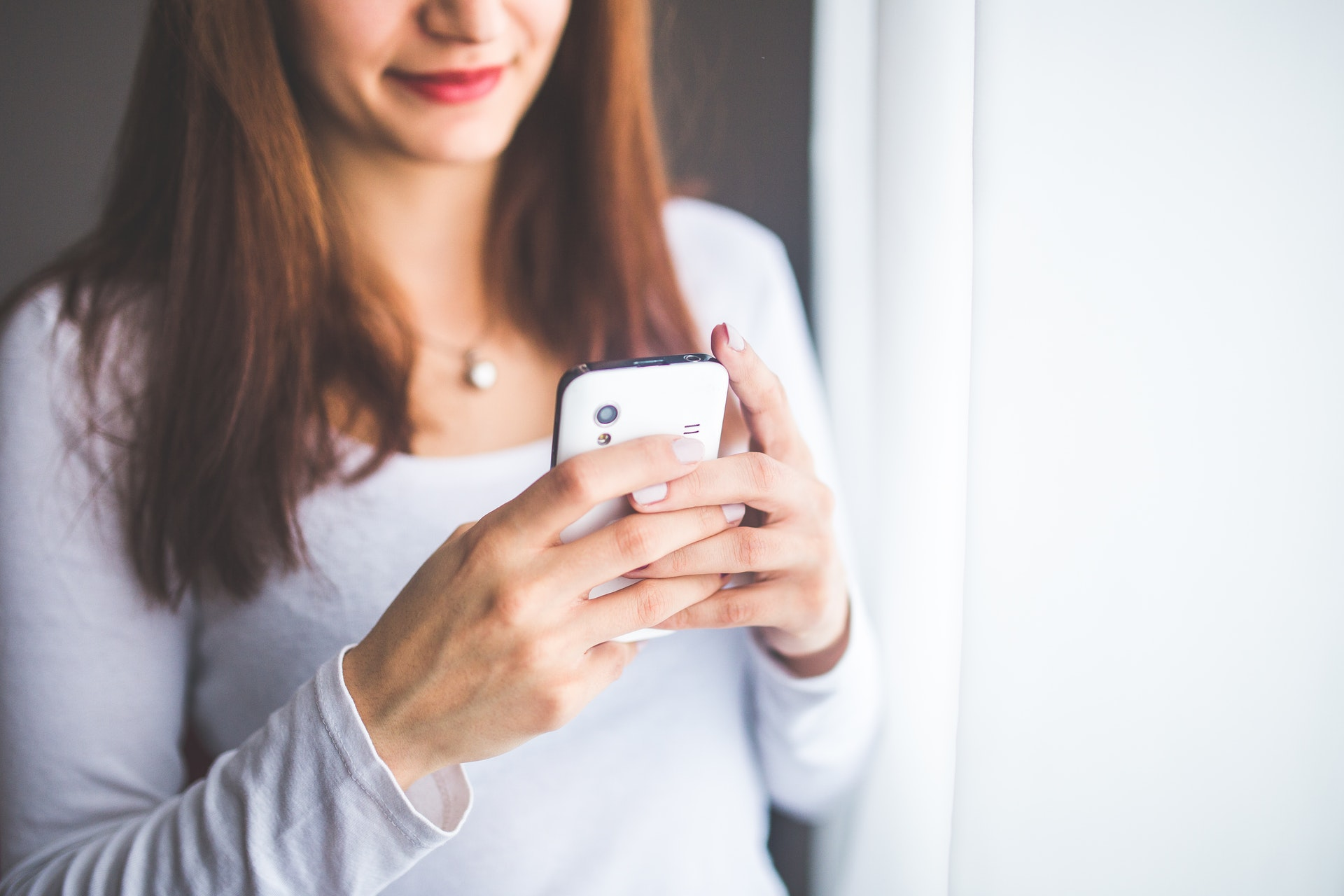 a woman in white shirt is using mobile phone for texting