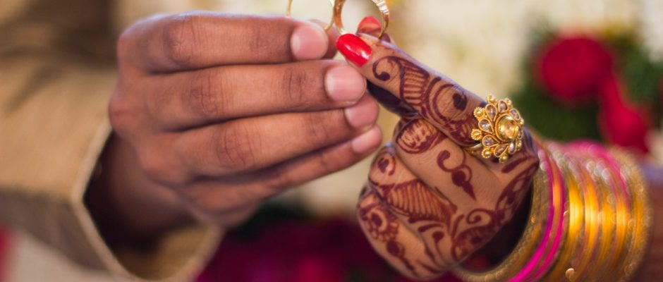 hands of a Hindu man and a woman holding wedding rings