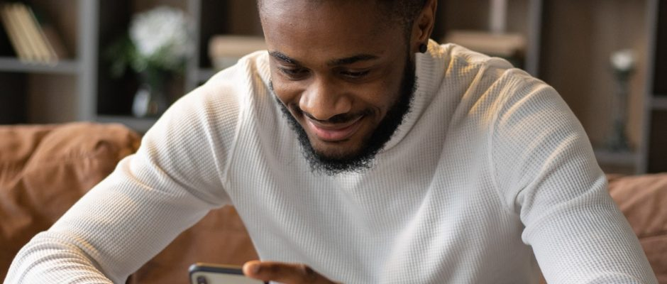 a smiling black man read cool online dating headline on sofa