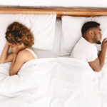 couple sleep separately on bed, partner doesn't want to be intimate