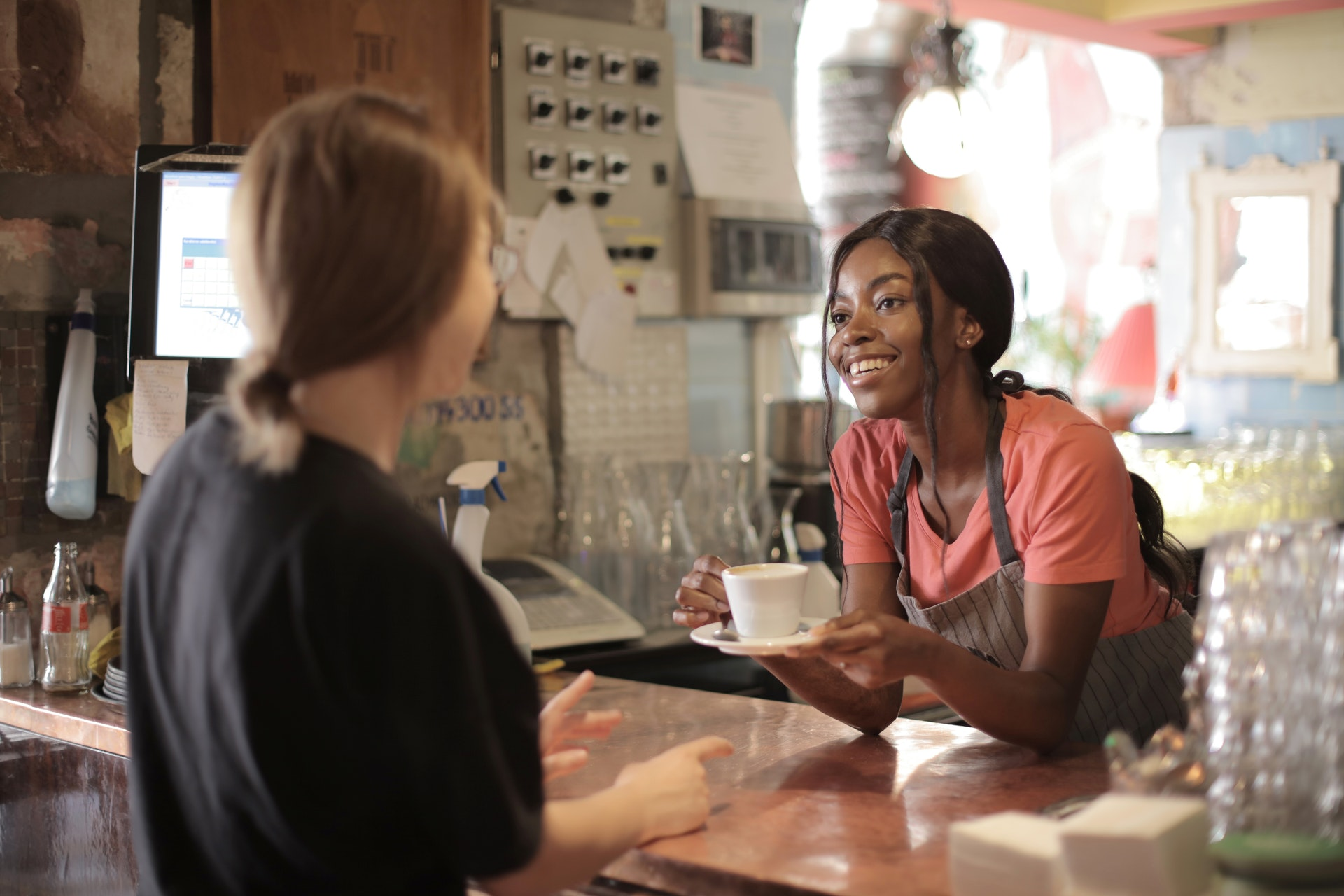 a female barista serving a cup of coffee to a female customer in a cafe