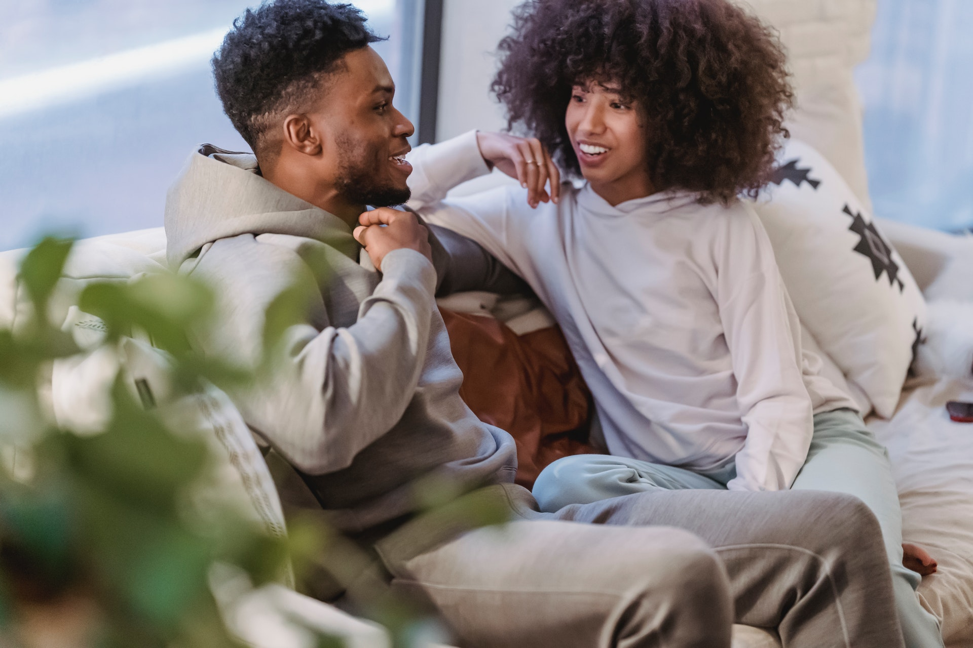 happy black couple in domestic clothes talking
