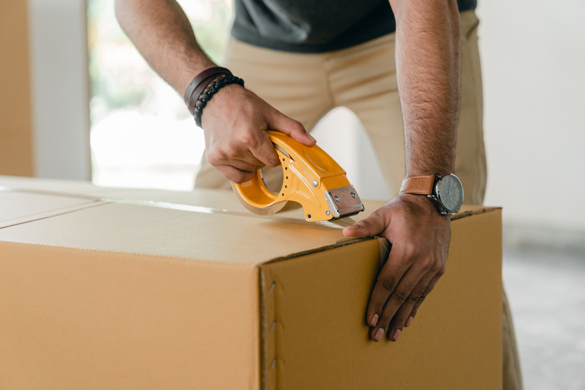 a man taping box with scotch, pack to move on