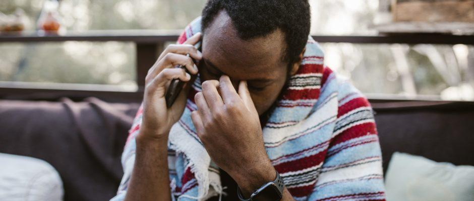 photo of a sad man talking on phone