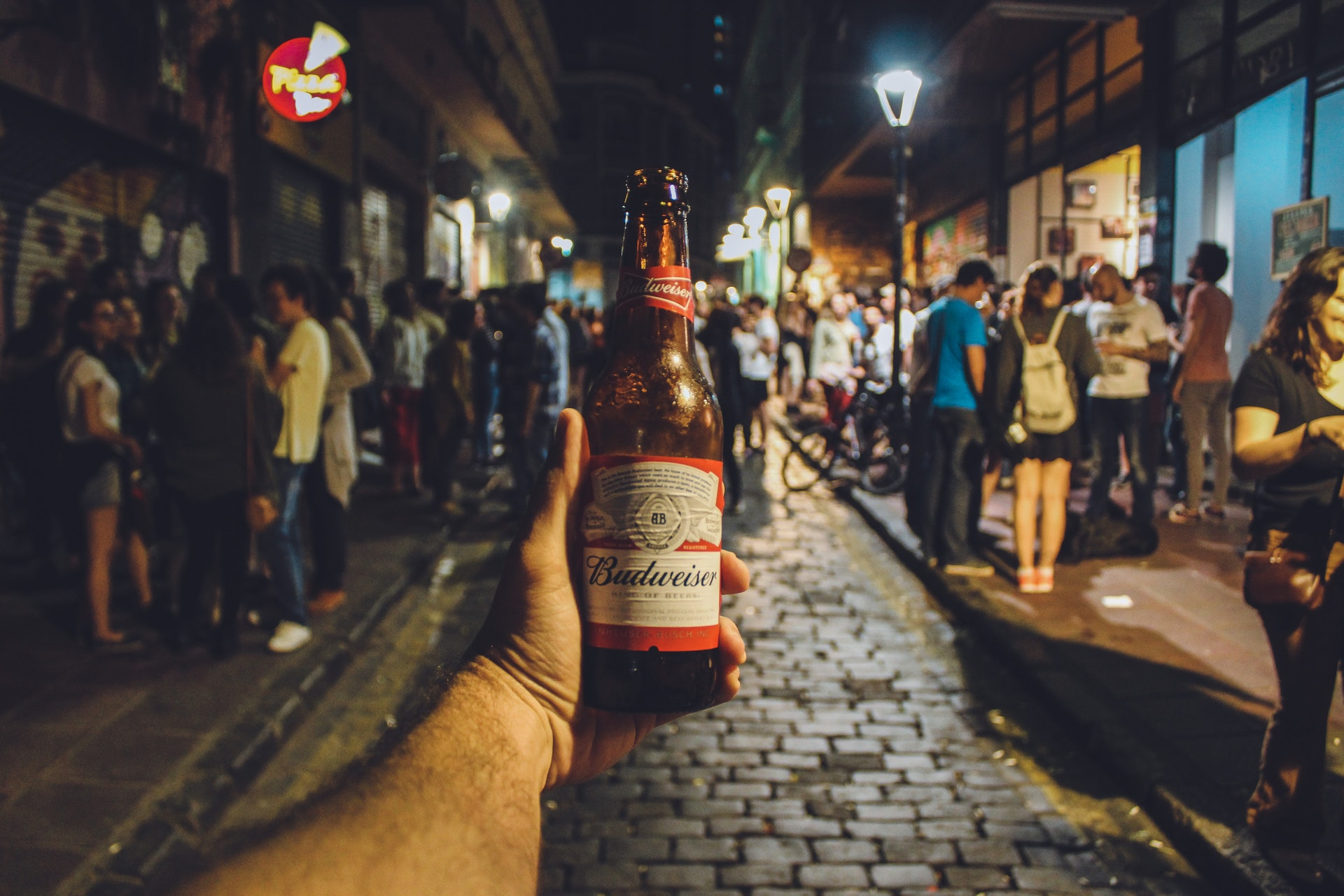 a hand holding a bottle of Budweiser in a bar crawl night